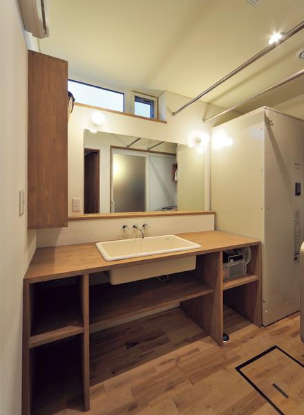 造作の洗面台、朝の忙しい時間帯でも使いやすいよう大きめに。高い位置に採光用の窓