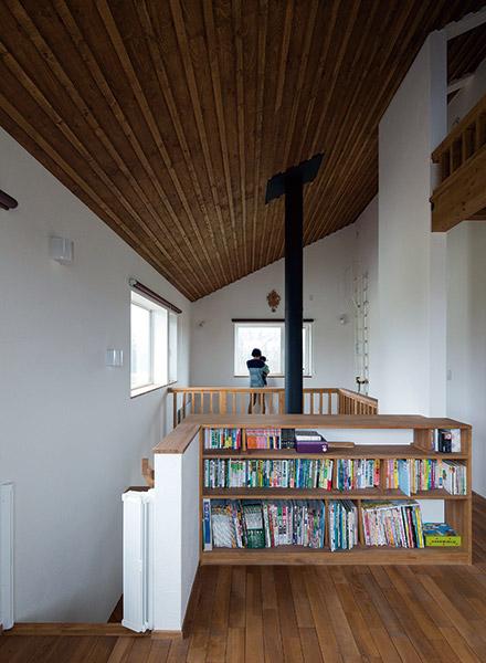 薪ストーブの煙突がアクセントになった吹き抜けが、住まい全体をひとつの空間につなぐ。腰壁は本棚を兼ねていてとても便利
