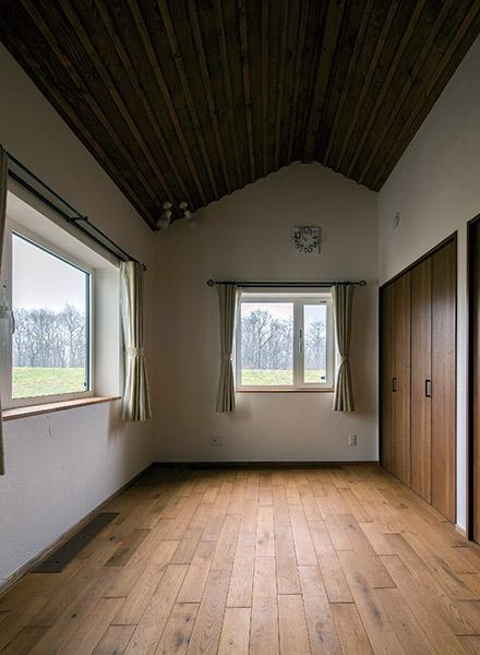 窓から自然風景を見渡せる子ども部屋。屋根の傾斜を生かした高い天井でゆとりのある空間