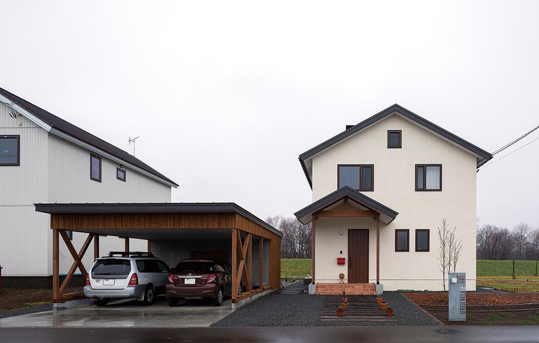 三角屋根のかわいらしい印象の住まい。2台分のカーポートは木製