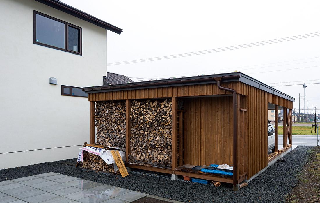 カーポートの裏は薪置き場を兼ねていて、薪割りやバーベキューができるコンクリートタイル仕上げのスペースもある