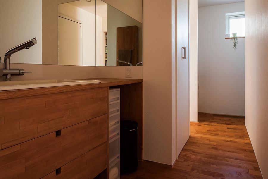 大きな鏡と角型シンクを備えた洗面台も造作。奥に見えるのは洗濯室を兼ねた脱衣スペース