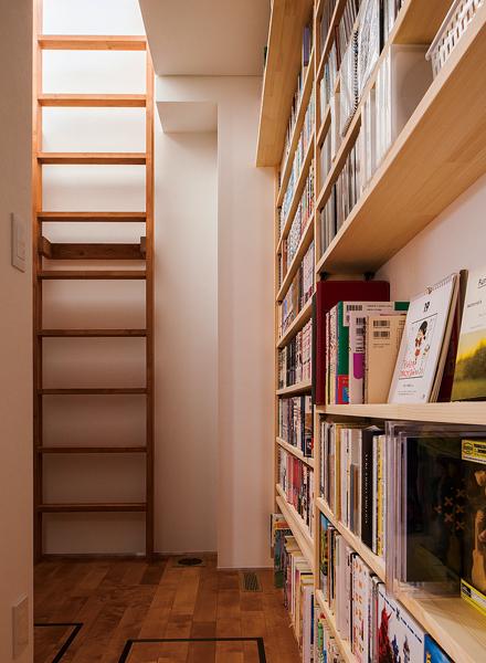 リビング横には書庫が設けられ、はしごを上るとSさんの書斎がある