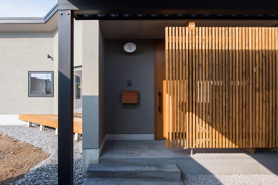 玄関ポーチには、目隠しと雪よけを兼ねたルーバーを設置。木の質感が、直線的なファサードにやさしさを添えて