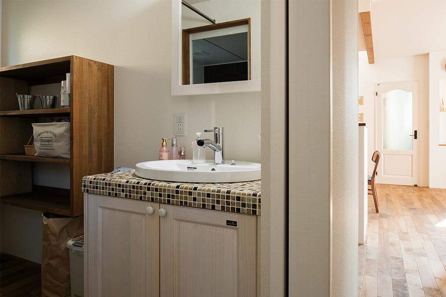 キッチンの裏側にレイアウトされたユーティリティには、モザイクタイルが美しいウッドワンの洗面台を採用
