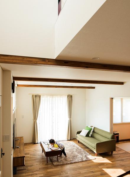梁を現しにして天井高を上げ、吹き抜け伝いに自然光がにじむリビングは、開放感たっぷり