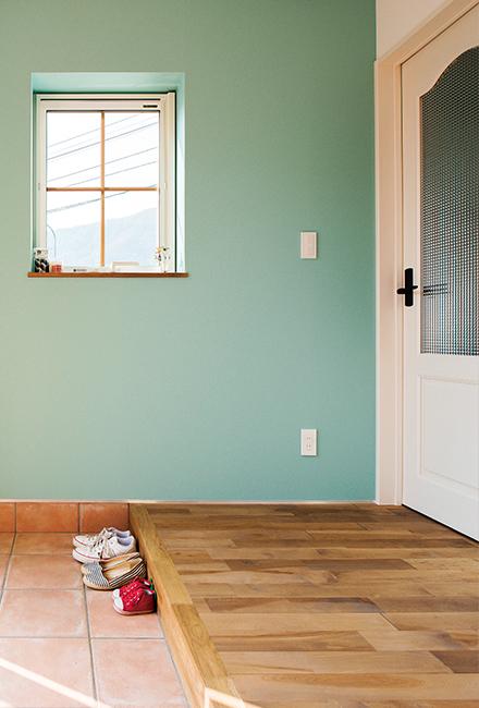 水色の壁とカバの無垢床、テラコッタタイルを採用した玄関ホール。土間仕様のシューズクロークも完備