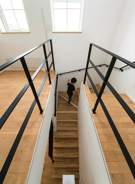 階段は黒いスチールの手すりがアクセントになっている。階段上部の窓からは、やわらかい光が1階に届く