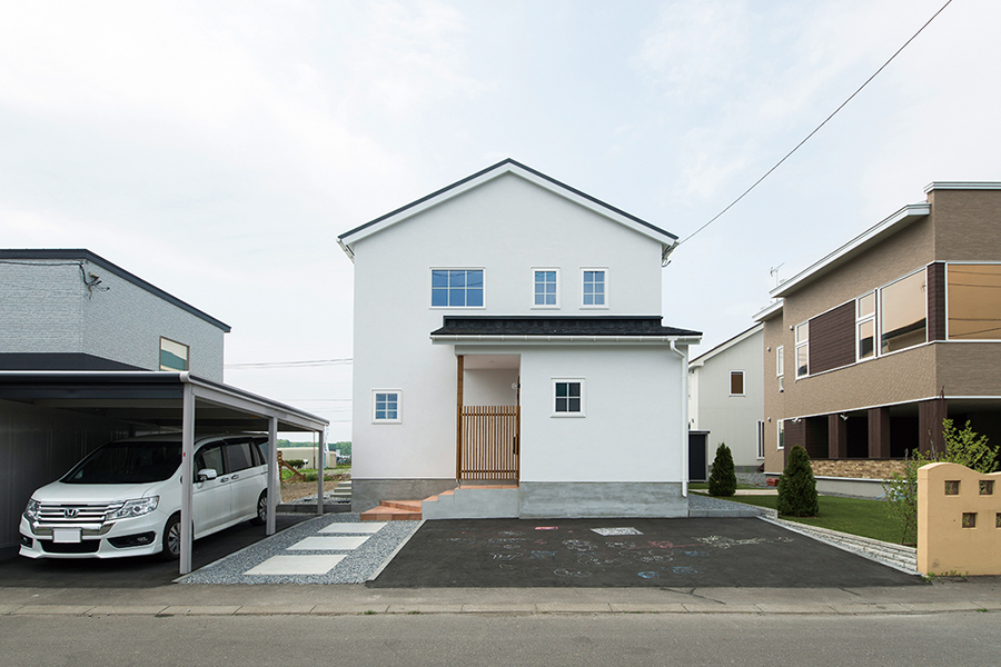 三角屋根のシンプルなフォルムの住まい。駐車スペースも広く確保している