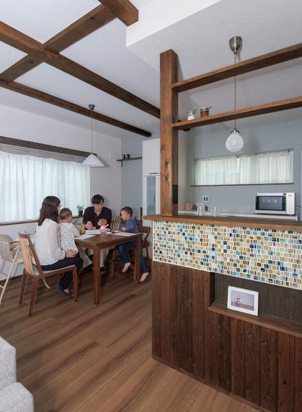 柱を生かしたカフェ風のキッチンカウンターにはアンティークなガラスタイルの装飾