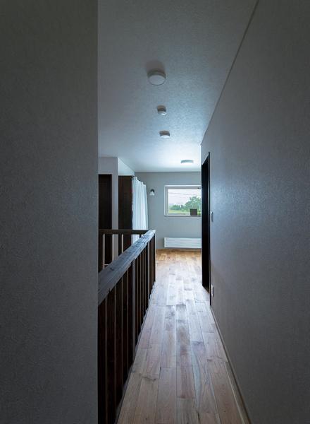 2階の床はクルミの無垢フローリングで、使い込むほど味わいが深まる居心地の良い空間に。目の前は開けた土手になっているため、窓の外には緑の木々や遊歩道の風景が広がる