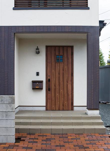 玄関ドアも古材の風合いがある木製に。レンガブロック敷きのエントランスとも馴染む