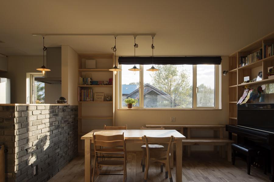 キッチンとダイニングの仕切りにはブロックを積み、造作家具やダイニングテーブルは木製に。自然素材が生きる空間