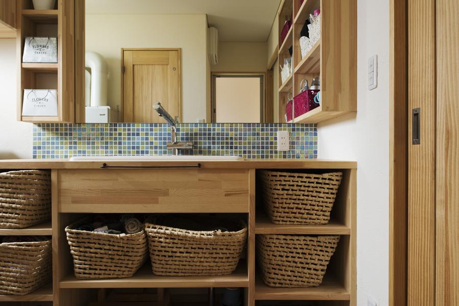 モザイクタイルがアクセントの洗面台にもたっぷりの収納。籐籠でモノをおしゃれに収納しているのは奥さんのセンス