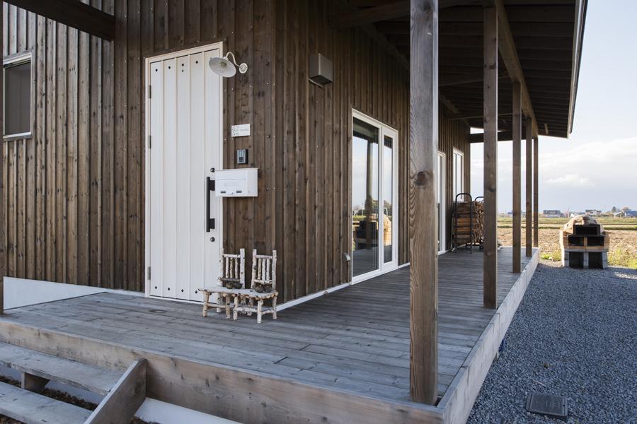 外壁は道産トドマツを縦張りに。フレンチカントリー調の玄関ドア、庇のあるウッドデッキはまるで外国の家のよう