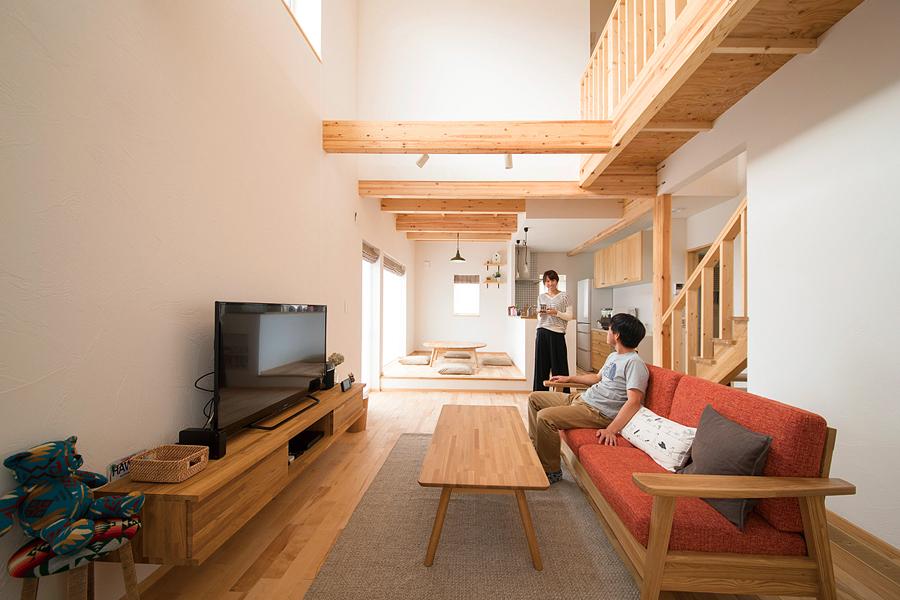 リビングの上は大きな吹き抜け空間。現しの梁や無垢の床材、キッチン背面の収納も明るい木の色で統一