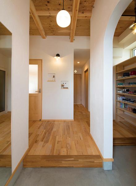 玄関横のシューズクロークはアール形状の入口をしつらえた。奥はトイレ、洗面脱衣室につながりキッチンへと回遊できる動線