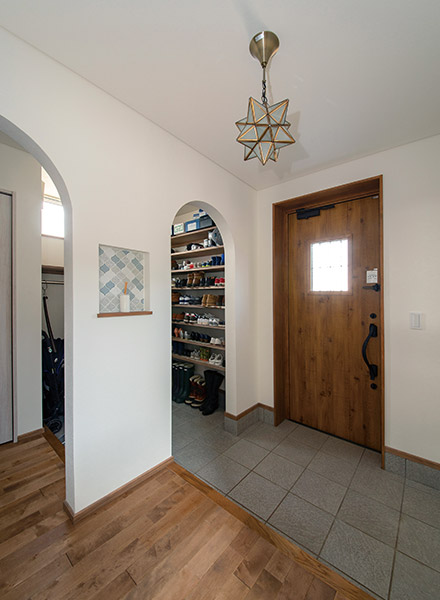 玄関まわりは、アールを描く開口部やタイルづかいでやわらかな印象に仕上げている