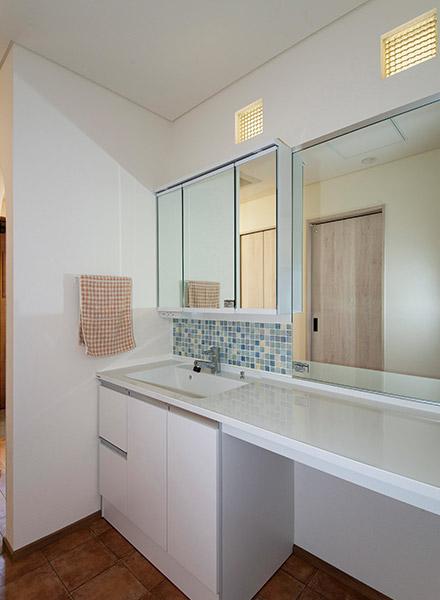 洗面スペースはモザイクタイルと、デザインガラスを入れた明かりとり窓で、レトロな雰囲気を演出