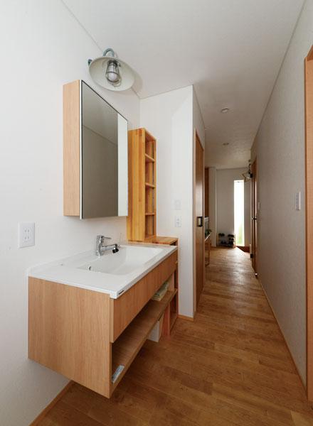 キッチンと学習コーナーを通ったら現れる廊下。突き当たりが玄関で、右写真のリビングへの廊下と回遊動線でつながっている。玄関・トイレと水まわりが短い動線で結ばれている