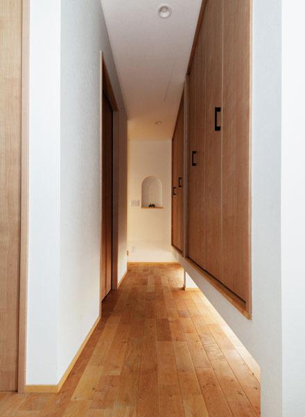 玄関から正面の小上がりとリビングにつながる廊下には、壁収納がしつらえられている。外光を採りこむ収納下の地窓は、北海道ハウジングの提案