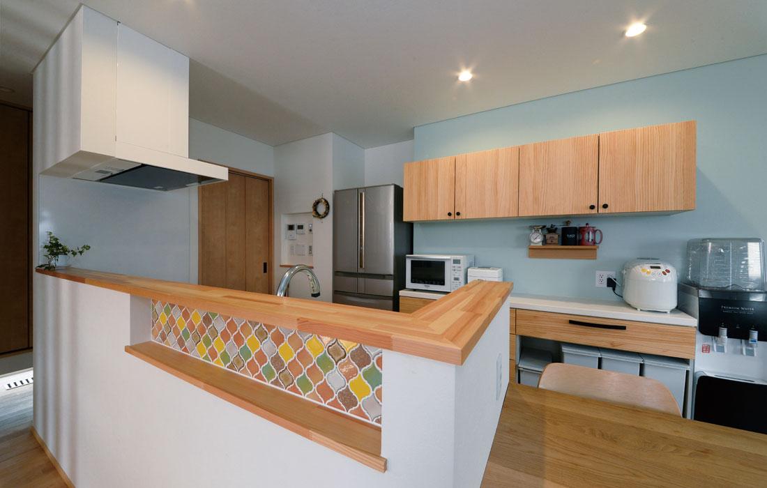 WOODONEのシステムを採用した対面式キッチン。手元をカバーするカウンターには、モザイクタイルを張り、空間のアクセントに