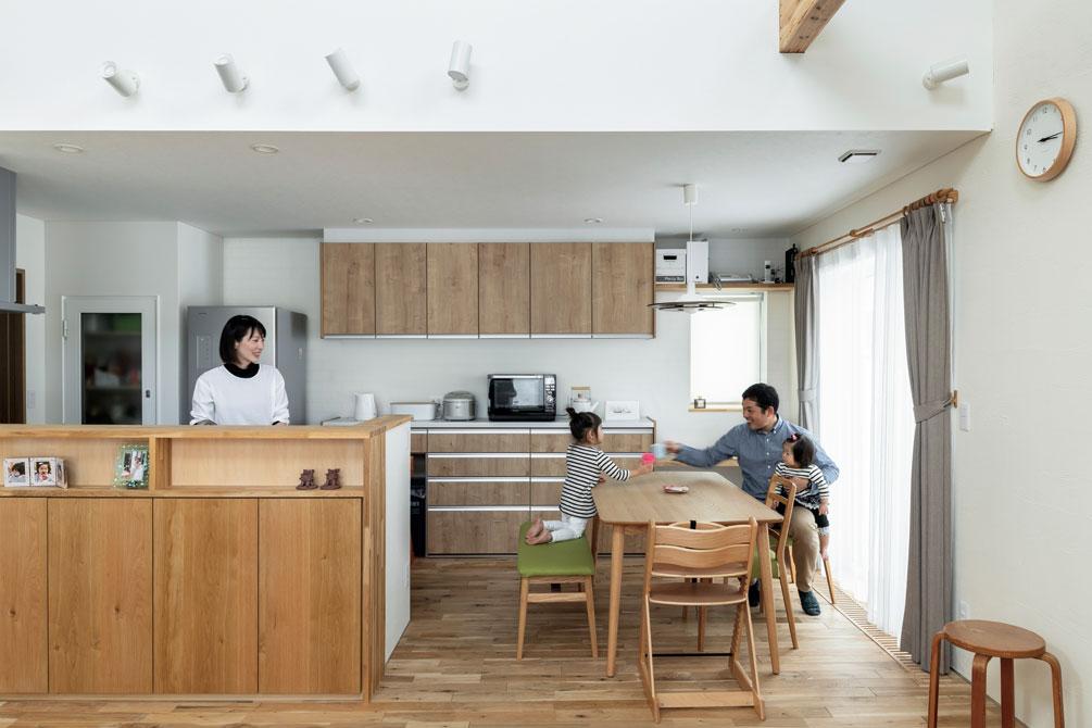 背面の収納棚や吊り戸棚に合わせ、キッチン前の腰壁の収納を造作し、統一感のある空間に