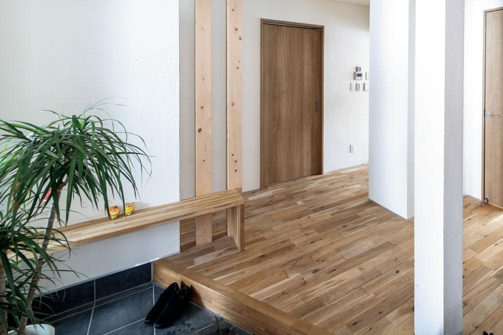 土間もホールもゆったりと広めで開放的な玄関。床に合わせて建具や造作ベンチも木で設えた