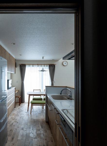 玄関ホールからダイニング・キッチンを望む。扉を開けてもすっきりとした景色が開ける