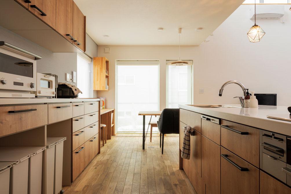 キッチンは夫婦二人で立っても楽に作業ができるよう、背面収納との距離を広くとった。ペンダント照明は奥さんがネットで見つけたもの