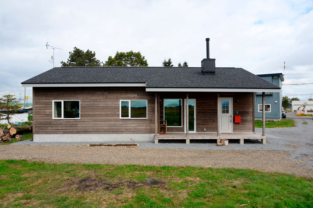 大屋根と薪ストーブの煙突、道南スギの外壁が田園風景に馴染む平屋の住まい。デッキを設け、濡れ縁風にしつらえた玄関ポーチは庭仕事の休憩や来客との語らいなど、多目的に利用できる