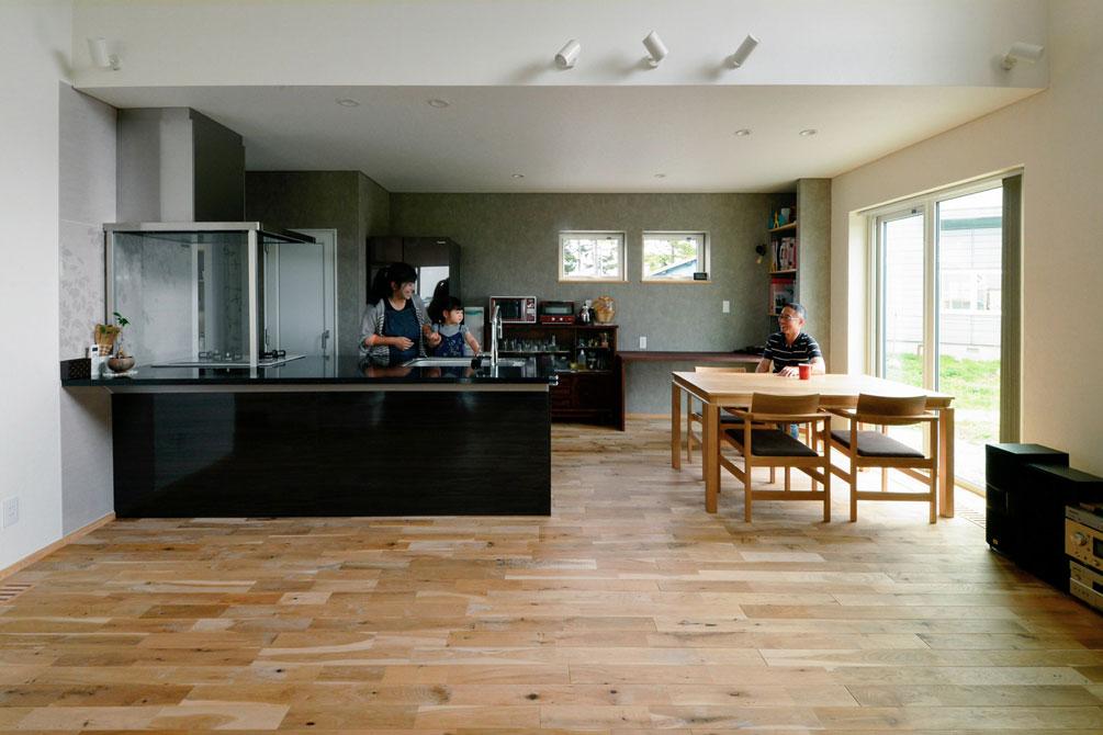 ナラの無垢フローリングと白を基調にしたのびやかな空間を、対面式キッチンの黒がほどよく引き締めて。ダイニングには、床と合わせたナラ材のテーブルと椅子を合わせた