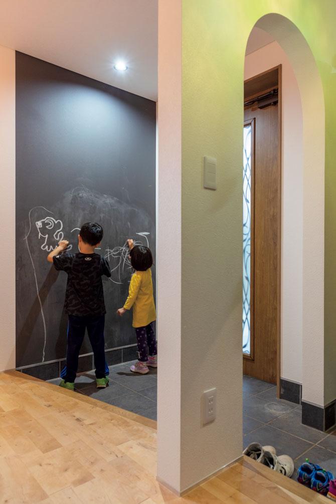 シューズクロークを備えた広々とした玄関の壁は、子どもたちがお絵描きを楽しめるように黒板クロスで仕上げられている