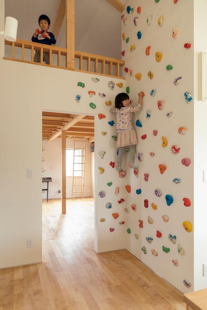 Yさんが「いろんな体験をさせたい」と、子ども部屋の入り口にクライミングウォールを設えた。子ども部屋の天井には、雲梯も設置されている