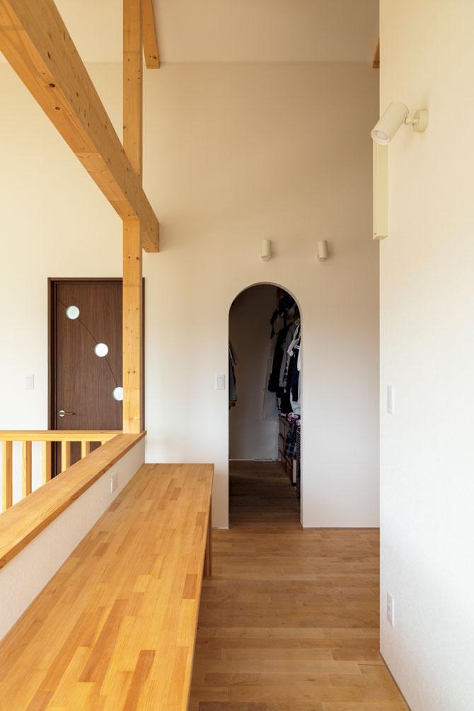 吹き抜けに面する階段ホールにも、多目的に利用できるカウンターがある。アールの出入り口の奥は、主寝室につながるウォークインクローゼット