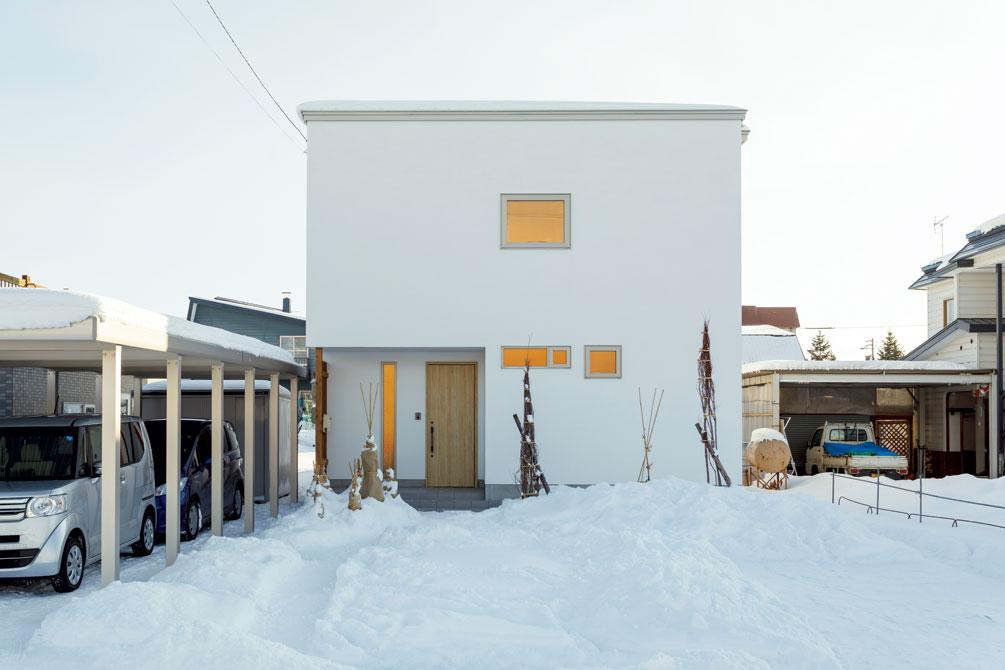 白い塗り壁が美しい外壁。雪のない季節になると、シンプルなこの外観に前庭の樹木が映える