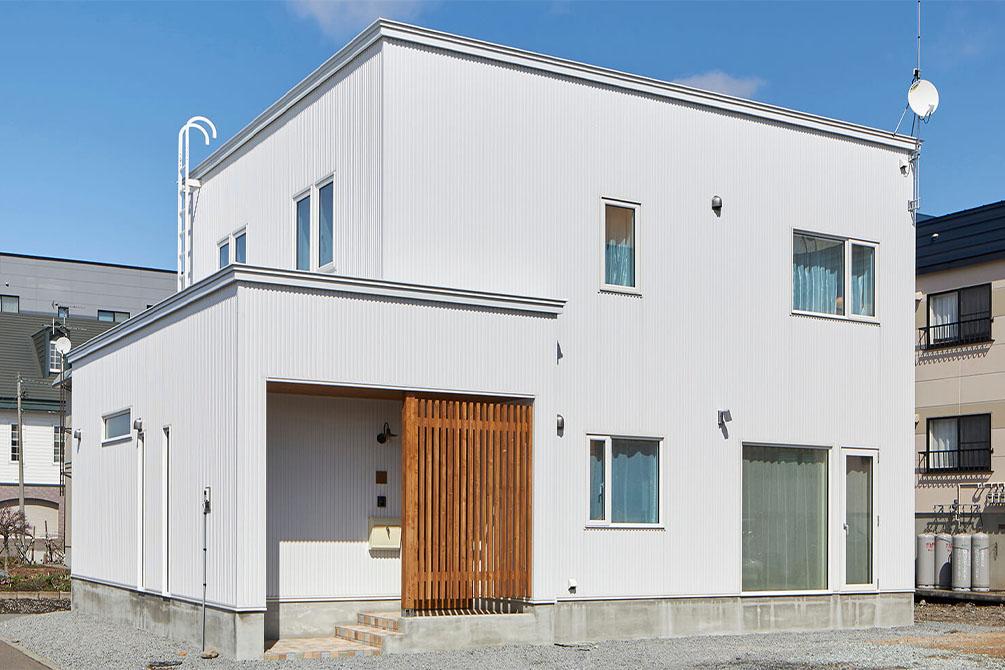 大きな道路沿いにあるTさん宅。青空に映える白いガルバリウム鋼板の外観が美しい。1階の突出した部分には水まわりが集約されていて、主な生活空間は奥側に位置しているため、車の音も気にならない