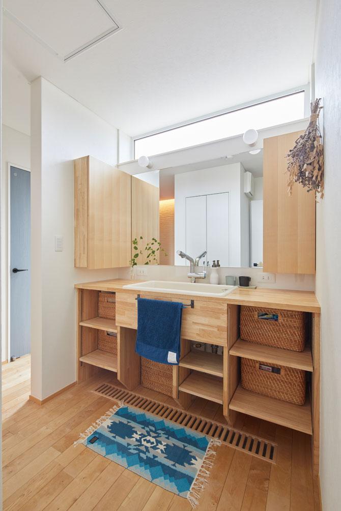 造作の洗面化粧台。上部の明かり採りの窓から陽光が注ぎ、明るく清潔感あふれる空間